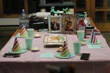 A table half-covered with a cheap plastic tablecloth and set with paper plates, cups, and party hats; in the middle is a cake and in the back are two photos in wooden frames