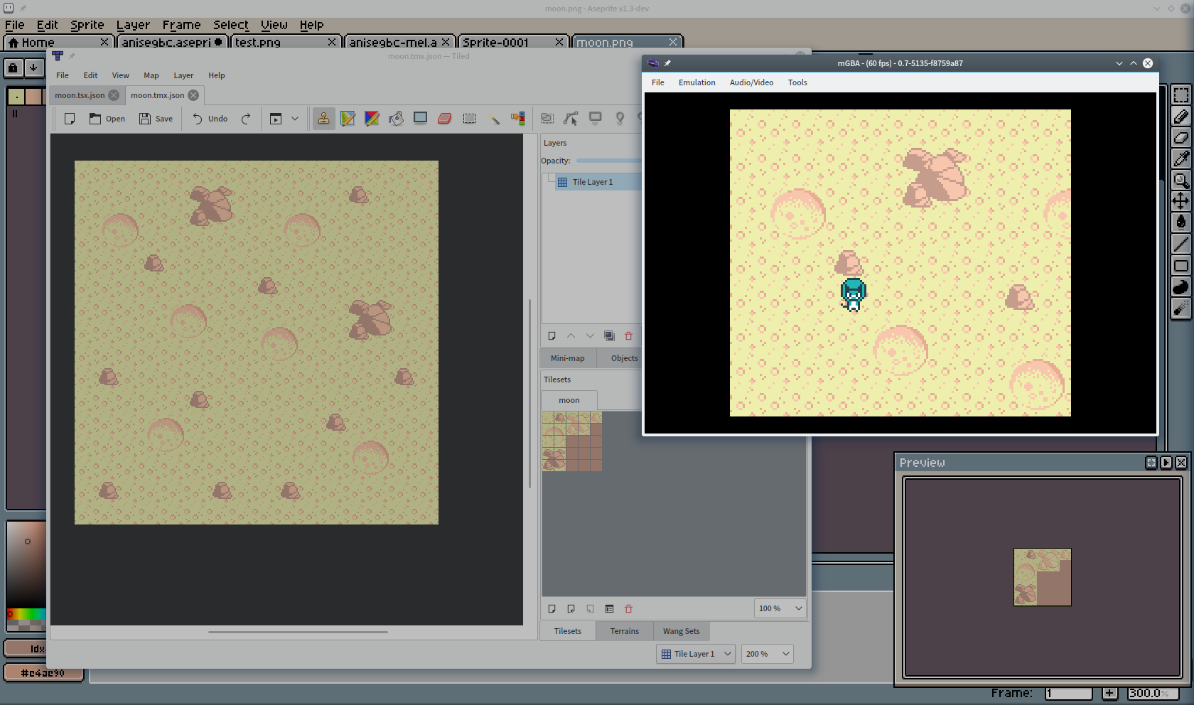 My desktop, showing the moon tiles in an image editor, the map put together in Tiled, and the game running in mGBA